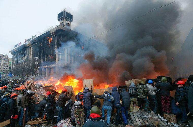 Протестующие держат щиты во время столкновений с силовиками при попытке разгона Евромайдан в центре Киева, 19 февраля 2014 года