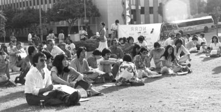 People seated on the grass outside the California State Building where the Los Angeles hearings took place. An NCRR banner is visible in the background.