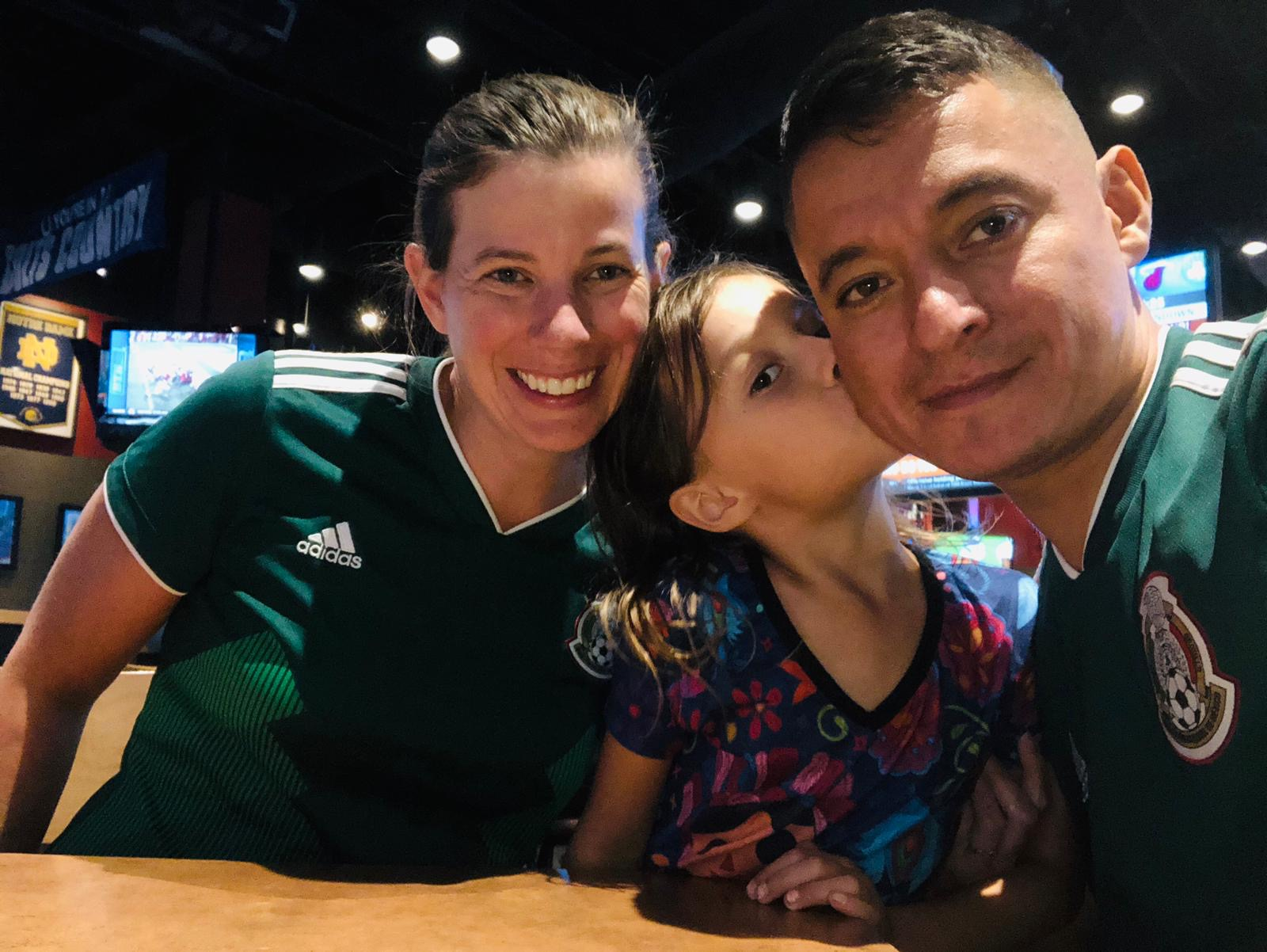 Amanda Crecelius with husband and daughter.  Amanda and husband are wearing Mexico soccer jersey and daughter is wearing a shirt with Mexican dolls.