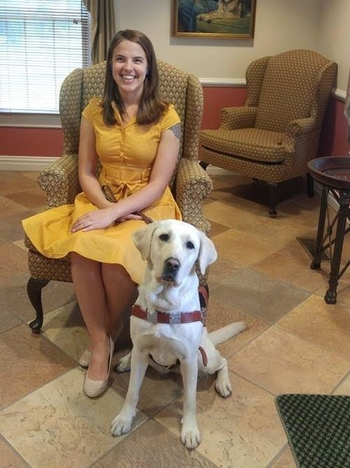 Abigail Shaw wears a bright yellow dress and a big smile; her guide dog, Kit, gazes quizzically at the camera
