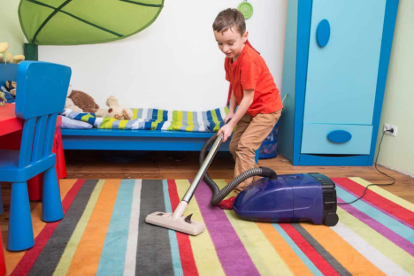little boy cleaning his room as a step towards being organized