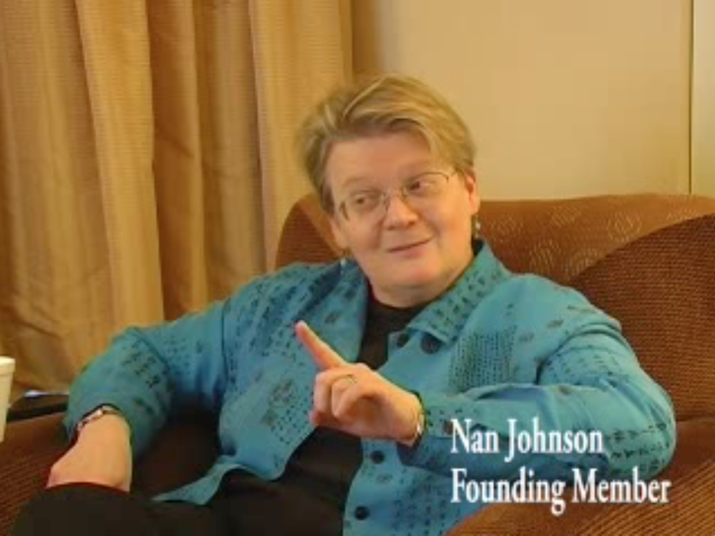 Image shows Nan Johnson sitting in a chair wearing a blue sweater. She is holding up her index finger in a gesture that suggests she is delivering an important point.