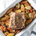 Roasted pork loin sitting on top of carrots and potatoes with a bowl of sautéed cabbage and apples on both sides