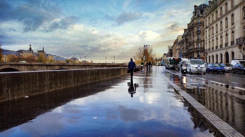 man walking along the sidewalk after it has rained
