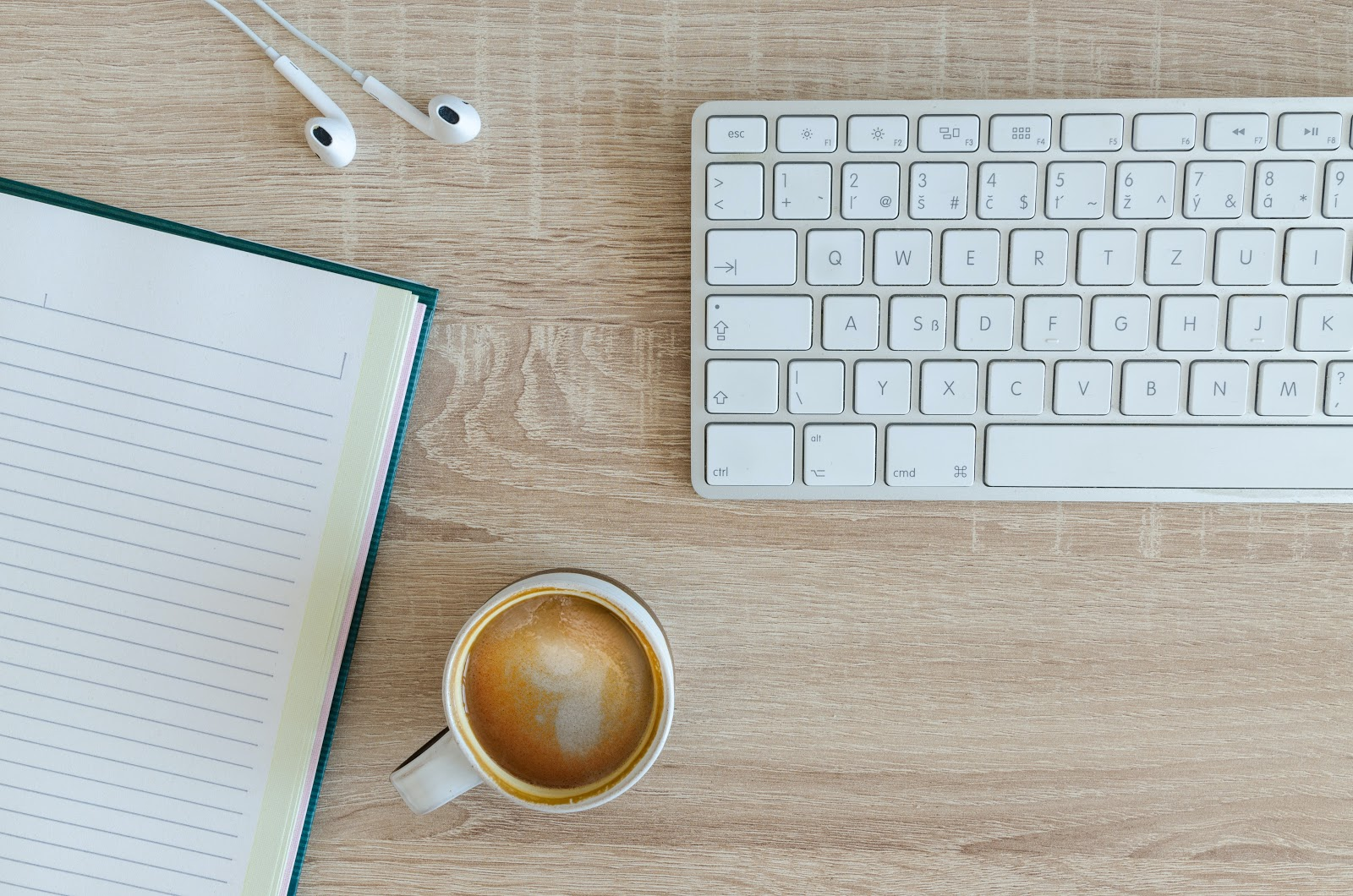 Keyboard, notepad, coffee cup and earbuds on a wooden surface.