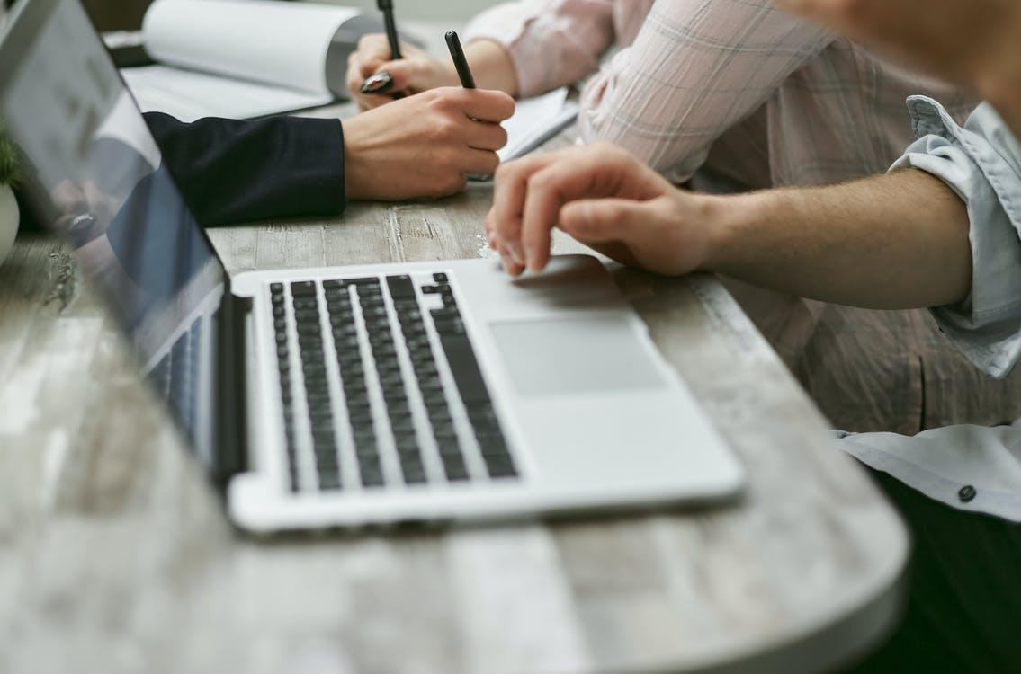 Crop faceless colleagues sitting at table while working on laptop and taking notes on documents with pen in light office