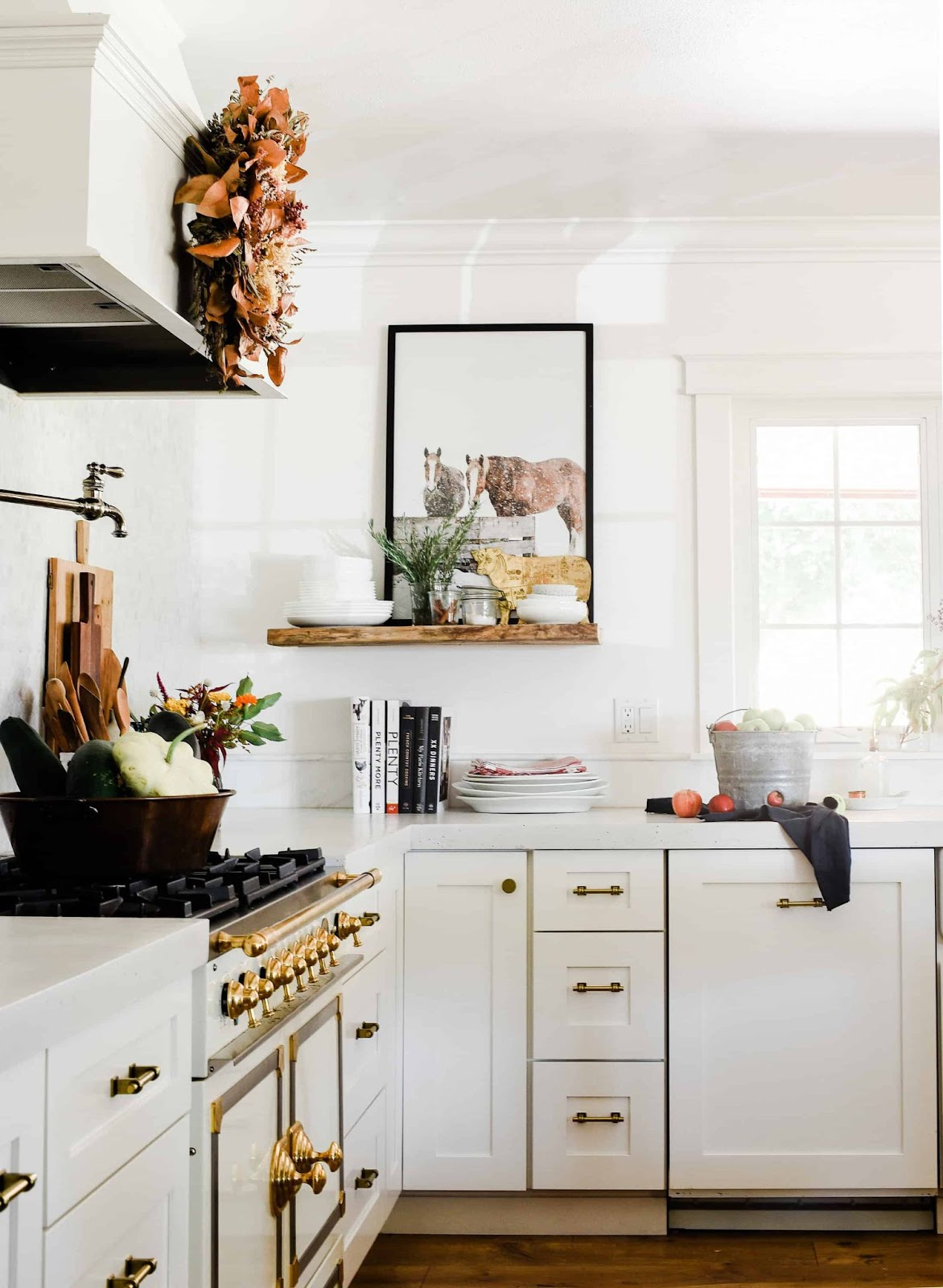 White kitchen setting with seasonal fall decor. Pumpkins and gordes and apples in a silver bucket.