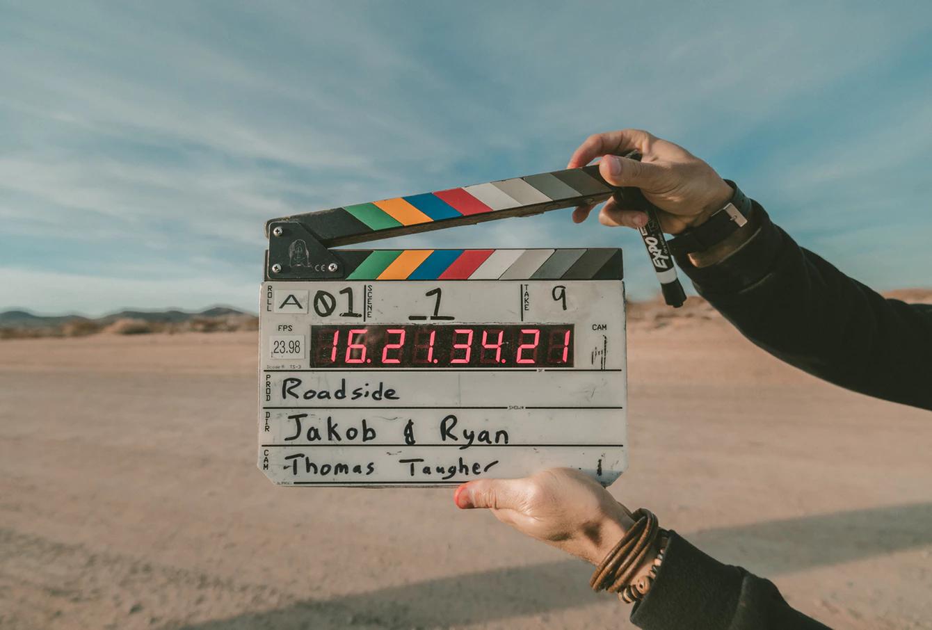 一雙手正準備打下電影開拍的板。
