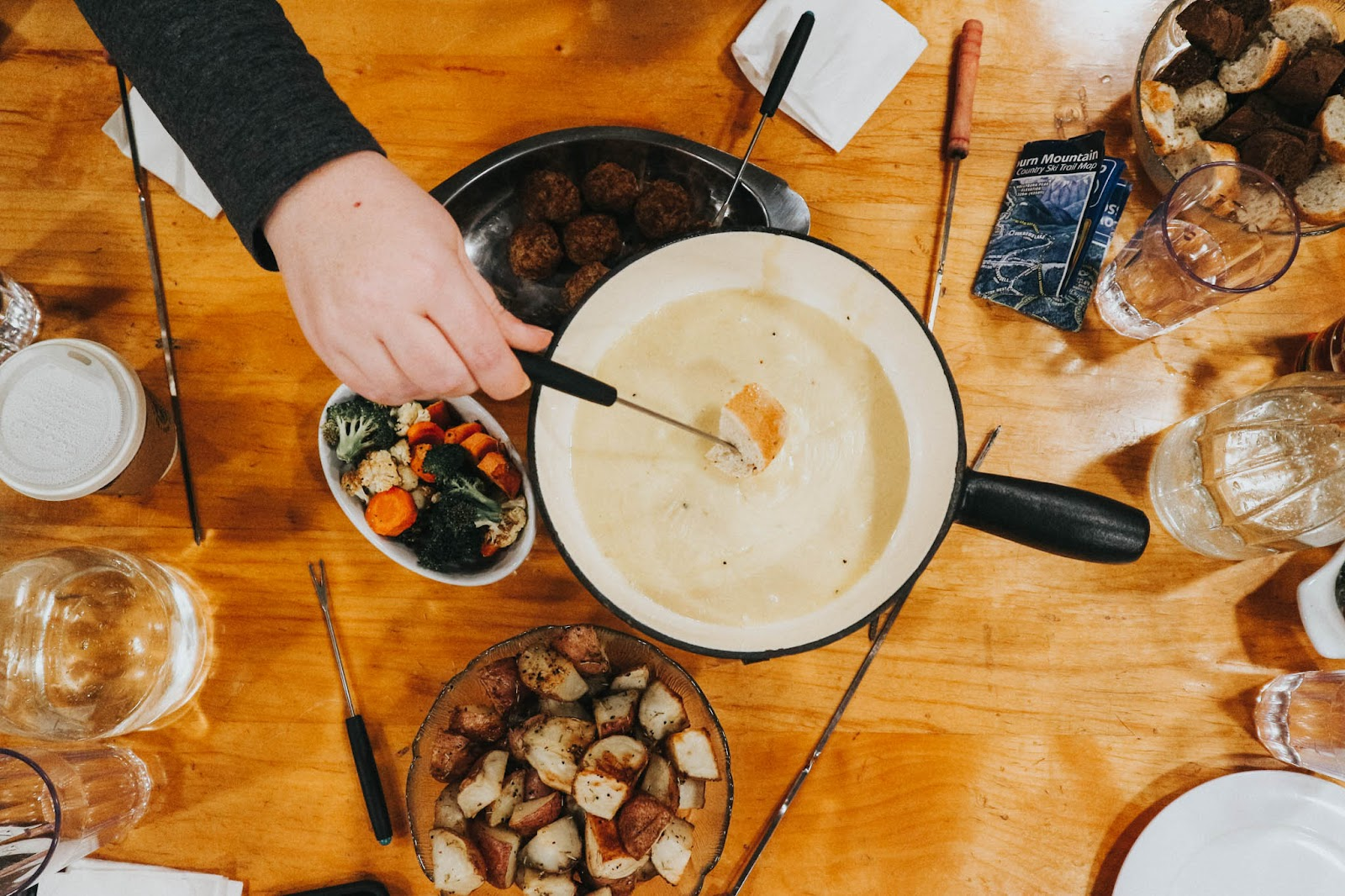 Table of fondue featuring cheese, vegetables and meat balls