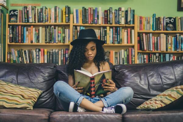 Mulher negra sentada lendo um livro.
