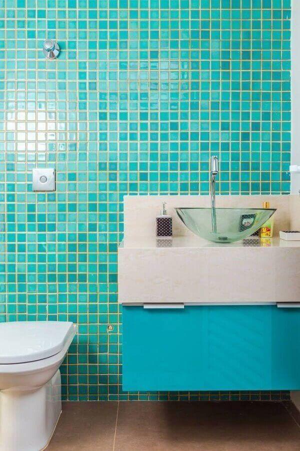Banheiro revestido com pastilhas verde água, armário azul, pia branca com cuba de vidro e piso de cimento quiemado.