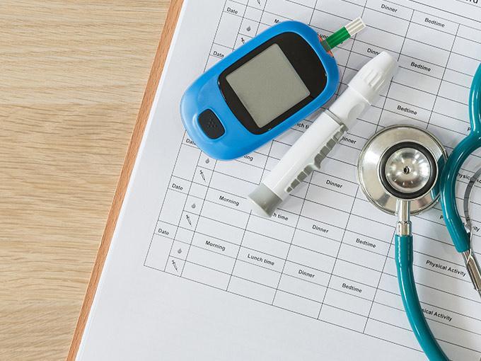 Ärztliche Überwachungs des Blutzuckerspiegels: Auf einem noch leeren Diabetes-Tagebuch liegen Blutmessgerät, Lanzette und blaues Stethoskop.