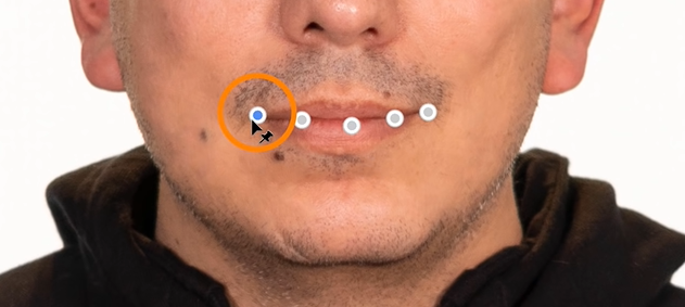 To make the subject smile more, click on the pin along the mouth's outer edge and drag it outward.