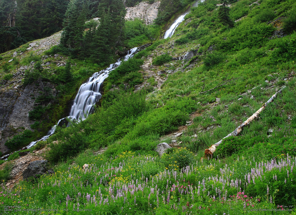 Vidae Falls cascading down the hillside at Crater Lake National Park with lush green grass surrounding on the Waterfall Road Trip near Klamath Falls.