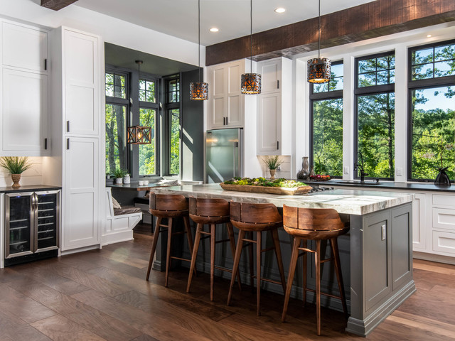 large kitchen flooded with natural light from three oversized windows. wood floors, bamboo barstools, white shaker cabinets and large wood overhead beams make the kitchen feel earthy and natural