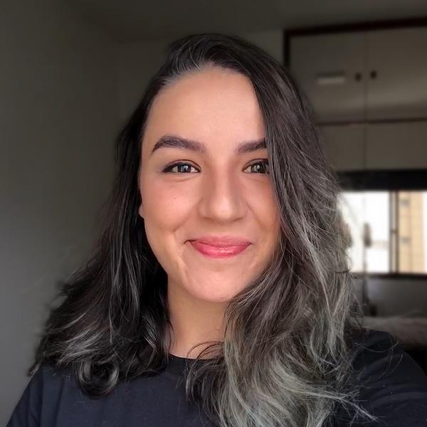 Uma mulher branca sorrindo para câmera com cabelos pretos, soltos e liso.