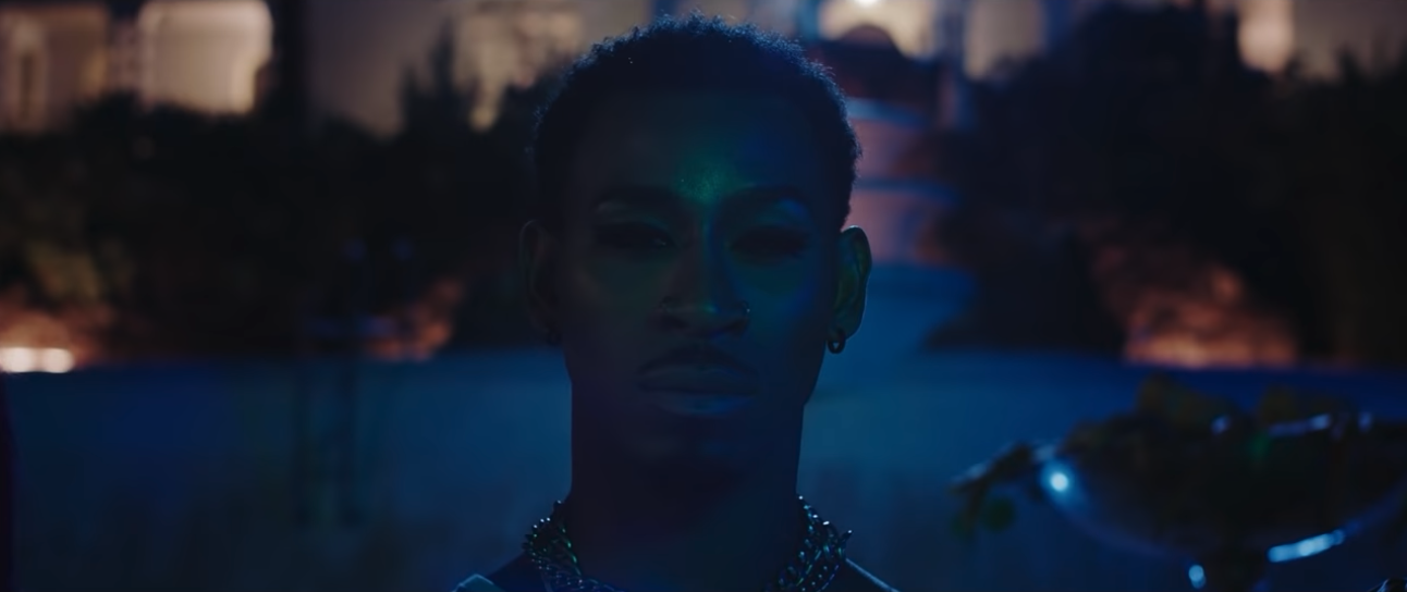 A close-up of a person's face at night. They are Black, have short hair, a mustache, and are wearing jewlery and make-up.