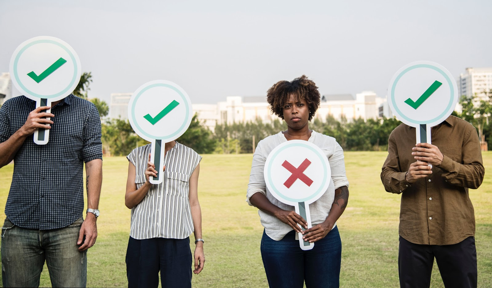 4 people holding up signs. The first two have a sign with a tick covering their face. The third has a sign with an X showing her face. The last with a tick sign covering their face.