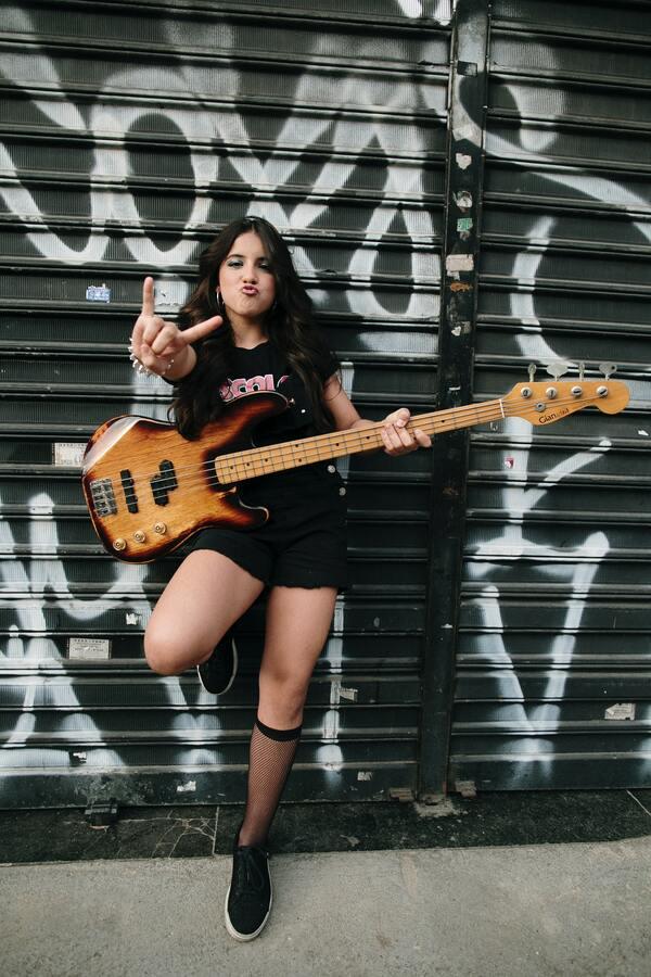 Foto de uma menina posando com uma guitarra e fazendo o sinal do rock