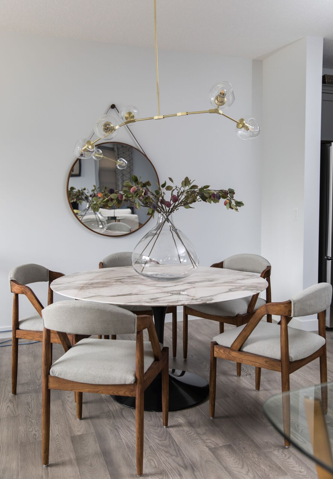 Calgary interior design leanne bunnell firm upholstered wooden chairs, marble top, gold branched modern lighting