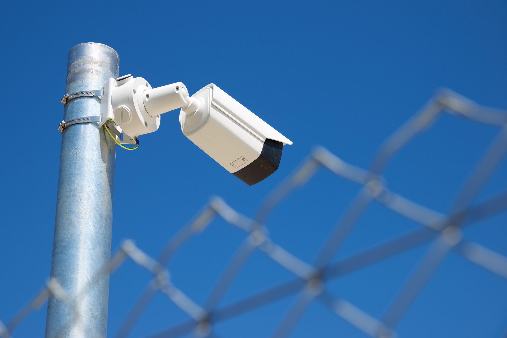 A surveillance camera along with temporary fencing