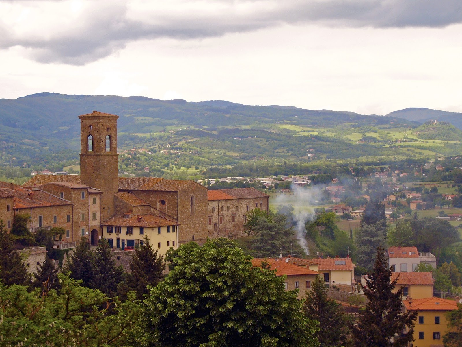medieval tower and buildings in poppi town surrounded by trees and green fields in tuscany italy on a cloudy day