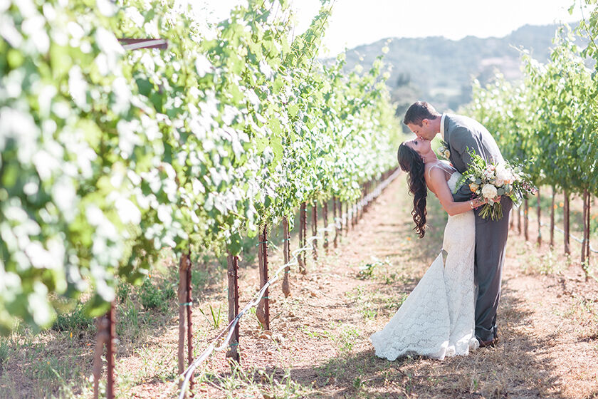 winery wedding vineyard with couple kissing