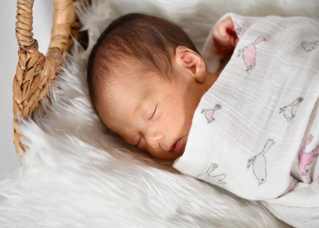 おくるみに包まれて眠る赤ちゃん