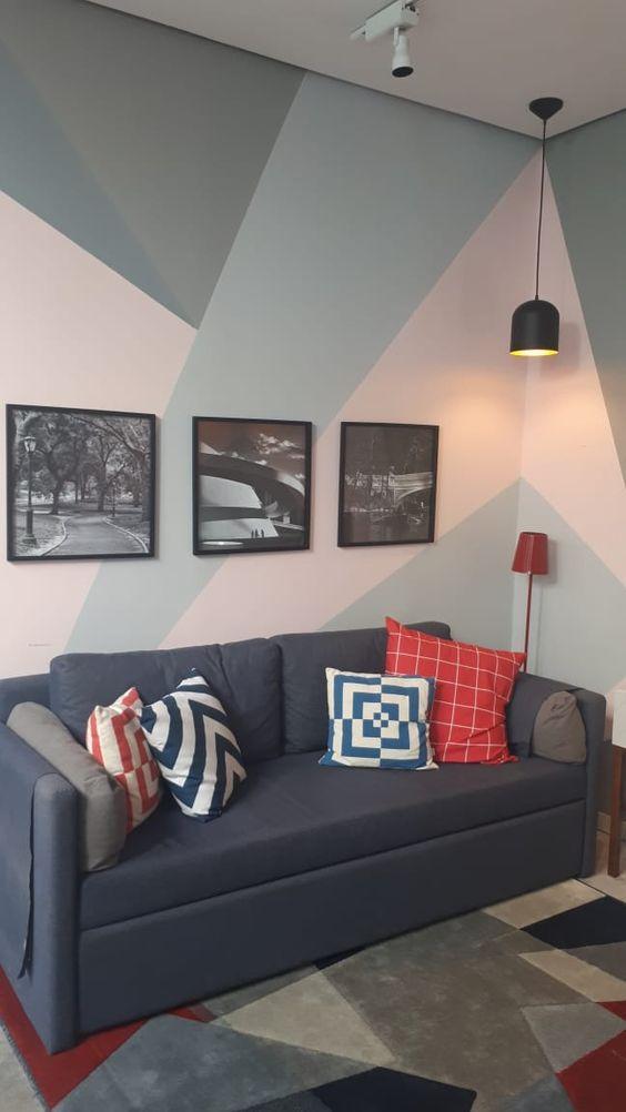 Sala de estar com pintura geométrica com cores leves e claras, harmonizando com decoração, cor de sofá piso e luminárias.