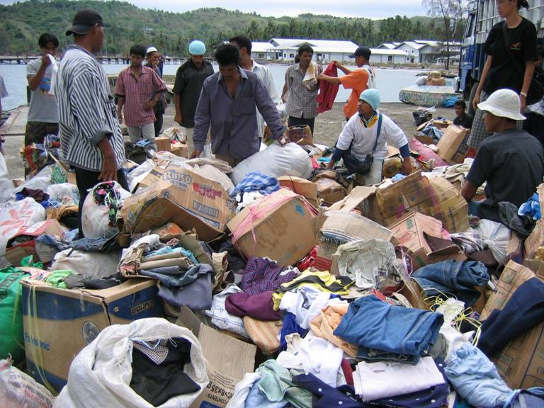 Several people sift through a large pile of donated clothing sitting on an Indonesian beach.