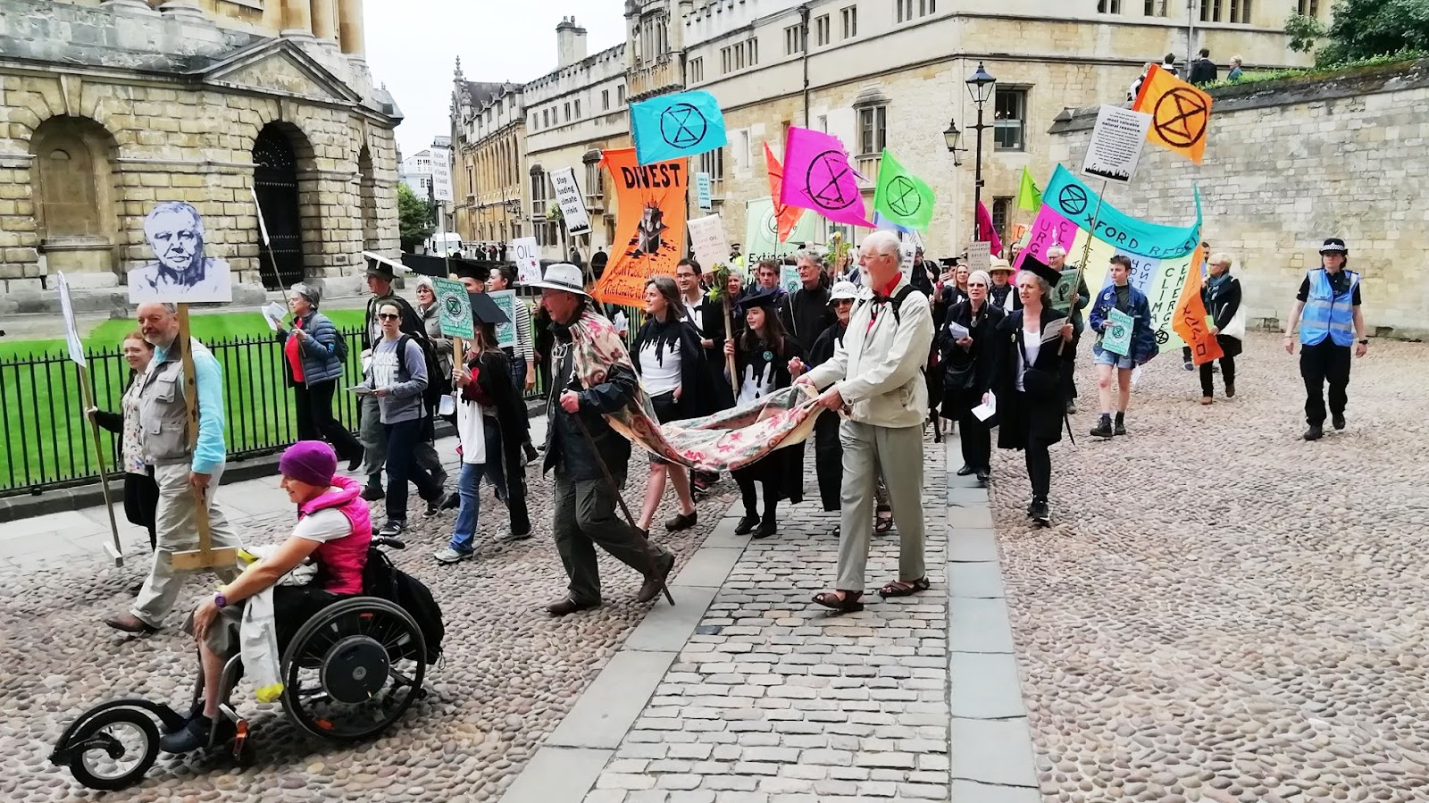 XR rebels processing around Radcliffe Camera, some with sub-fusc, some with XR flags.