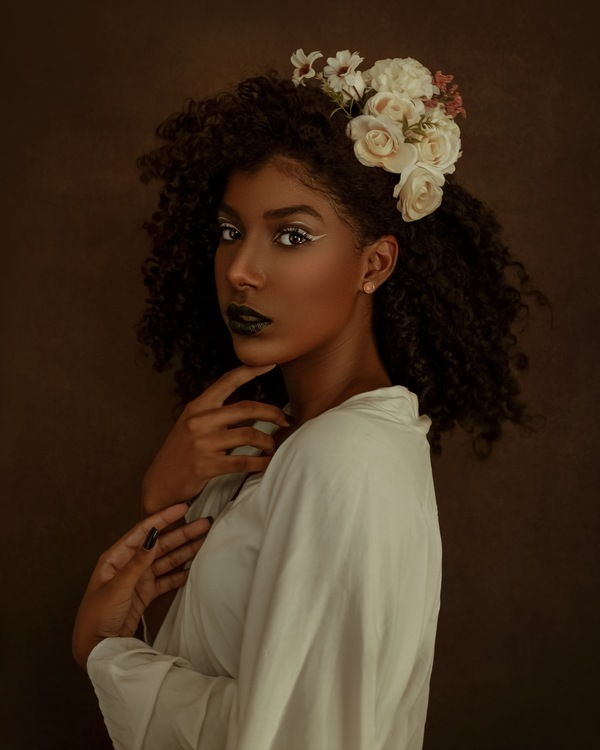 foto de uma mulher negra com a mão no queixo e uma flor no cabelo