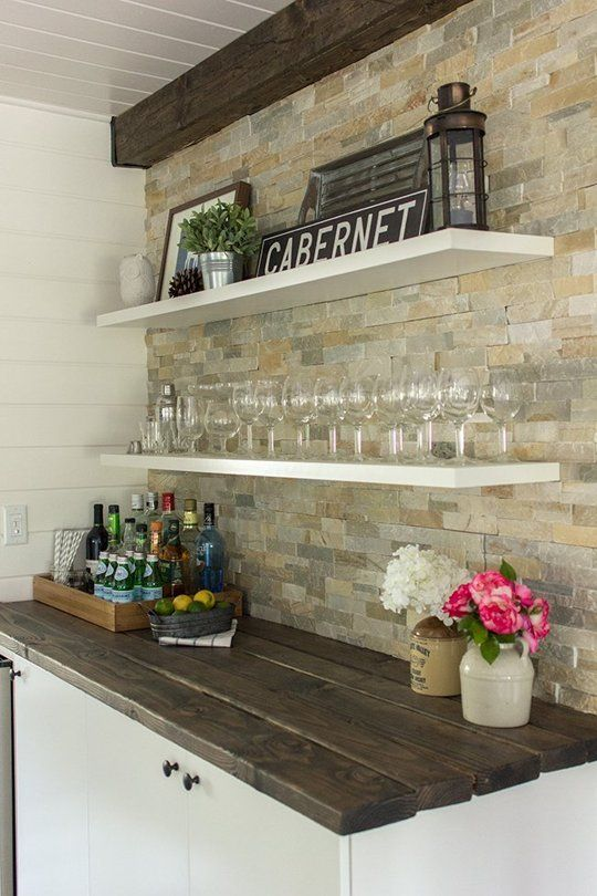farmhouse drink bar with white floating shelves, rustic signs, shiplap, distressed wood countertop and large mosaic stone tile backsplash