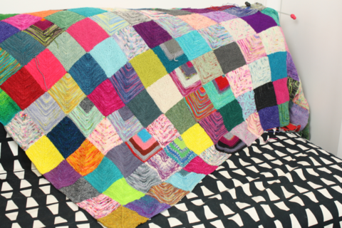 a multicoloured square blanket sitting on  a patterned black and white sofa.