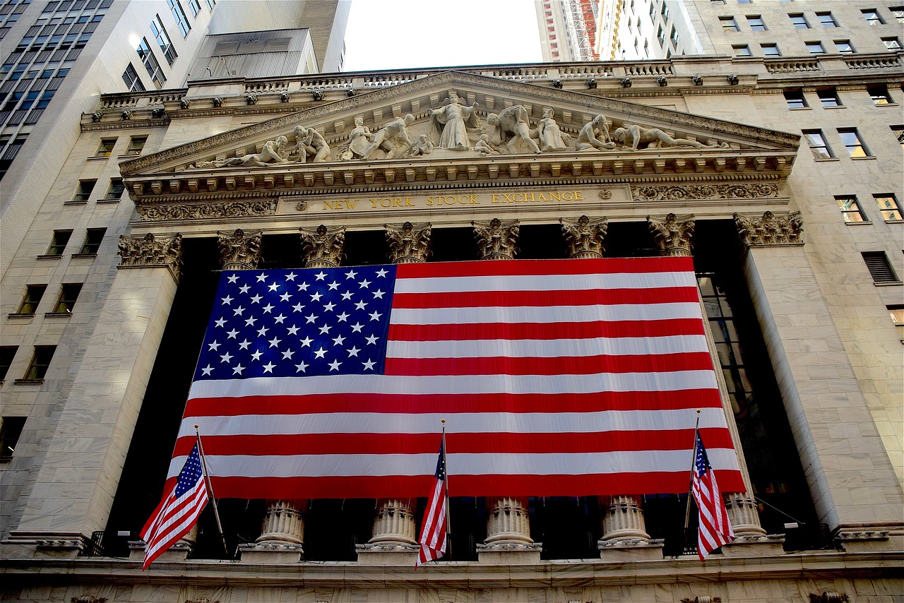 The front of the New York Stock Exchange, displaying one big American flag and three smaller ones.