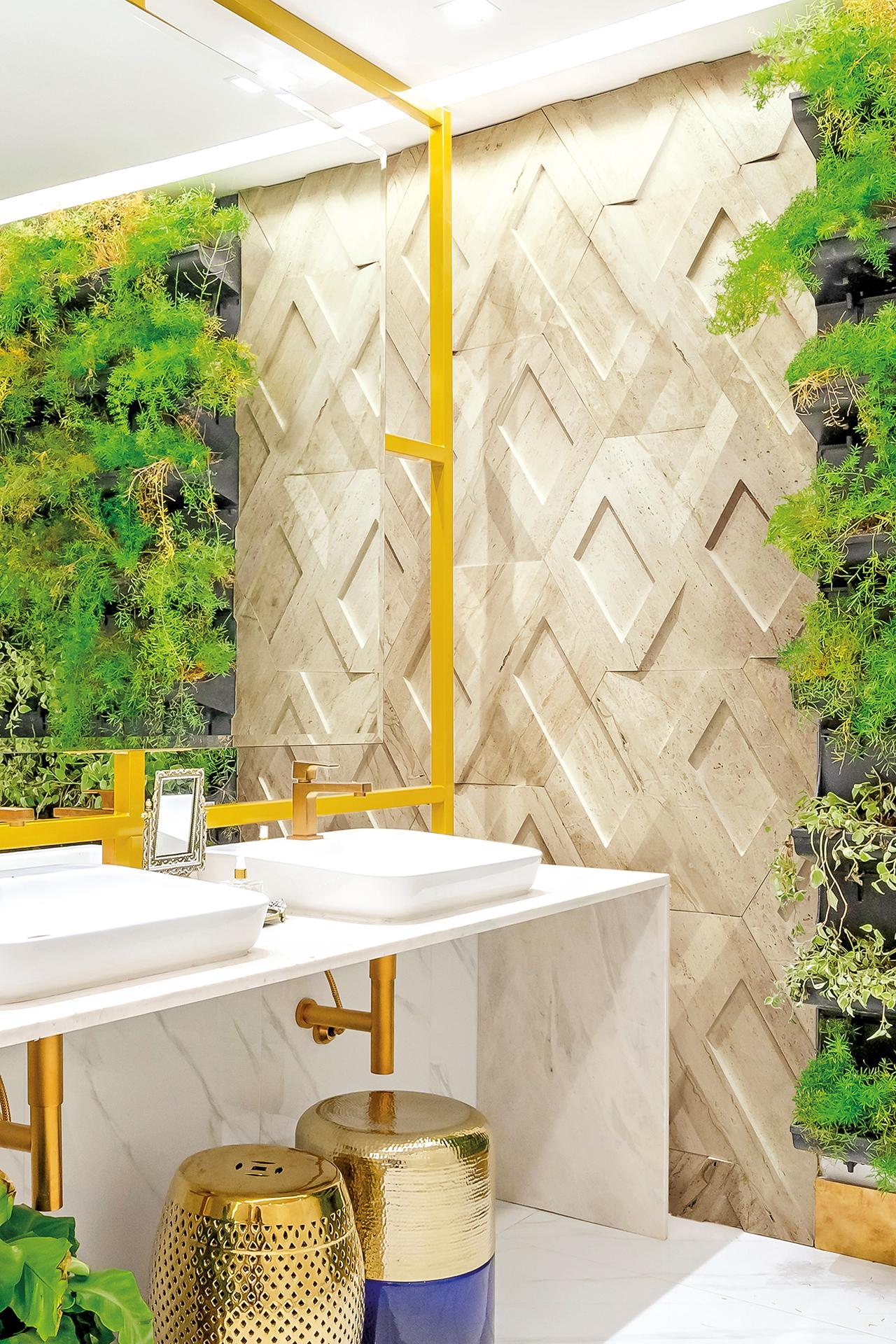 Banheiro com piso porcelanato branco, bancada da pia e cubas brancas, espelho com moldura dourada combinando com torneiras, parede lateral com jardim vertical e revestimento 3D da linha Infinity