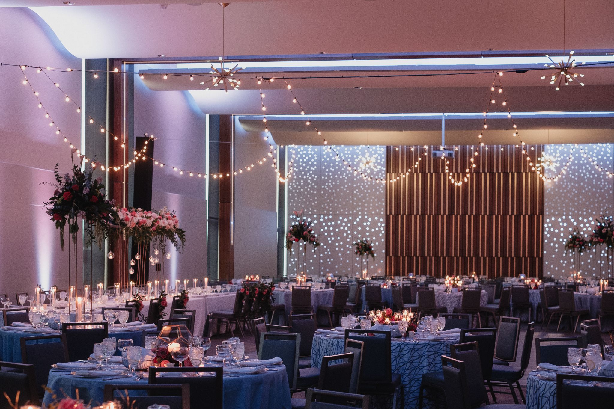 A large indoor wedding venue event with tables, lighting and decor.
