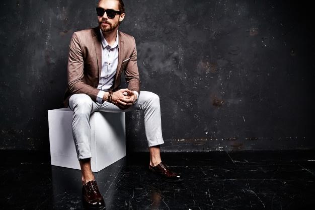 Portrait of handsome fashion stylish hipster businessman model dressed in elegant brown suit sitting near dark