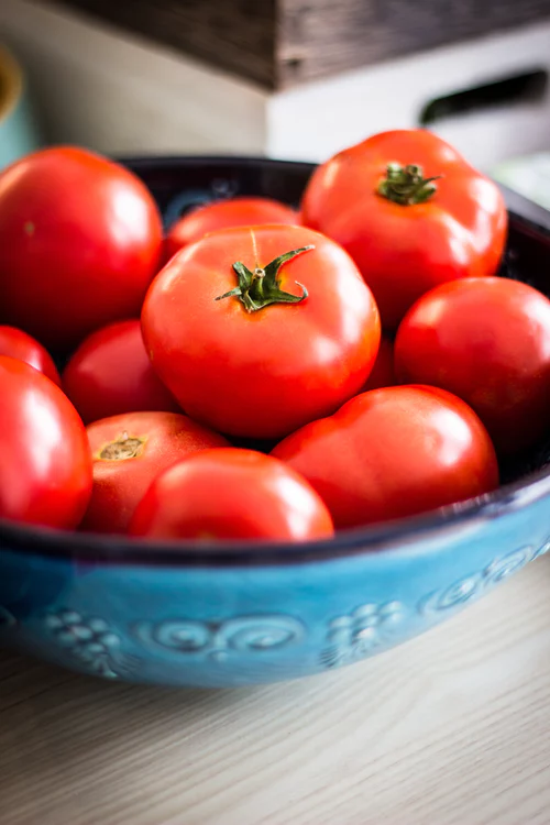 A bowl of tomatoes on a countertop.