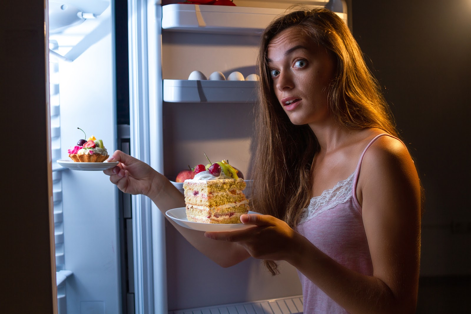 What foods should be avoided with SIBO: Woman removes desserts from fridge at night