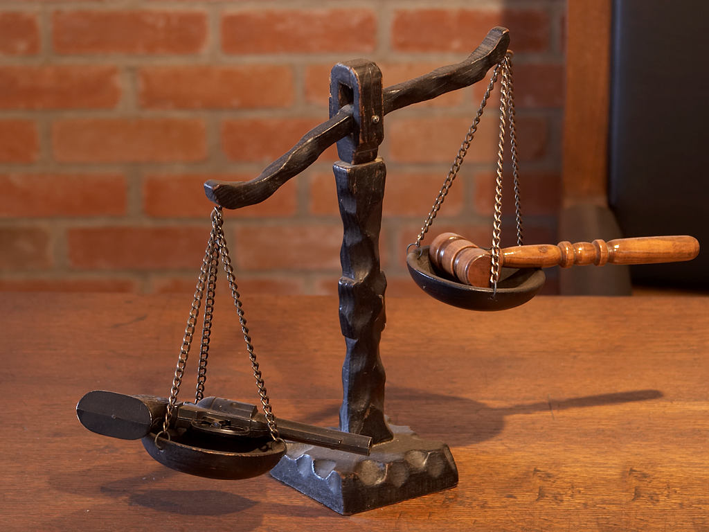 Scales of justice with gun on one side, legal gavel on the other