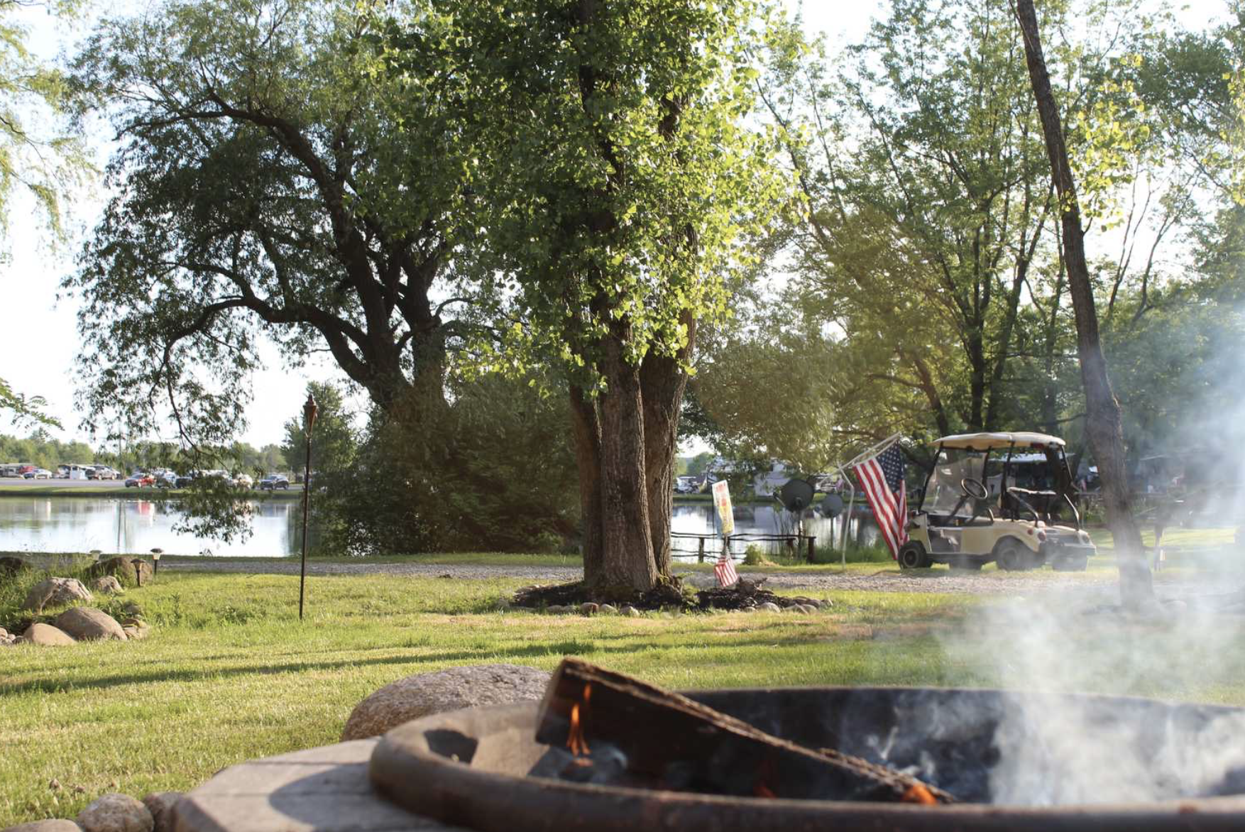 Photo of campground in front of campfire with golf cart in the background.