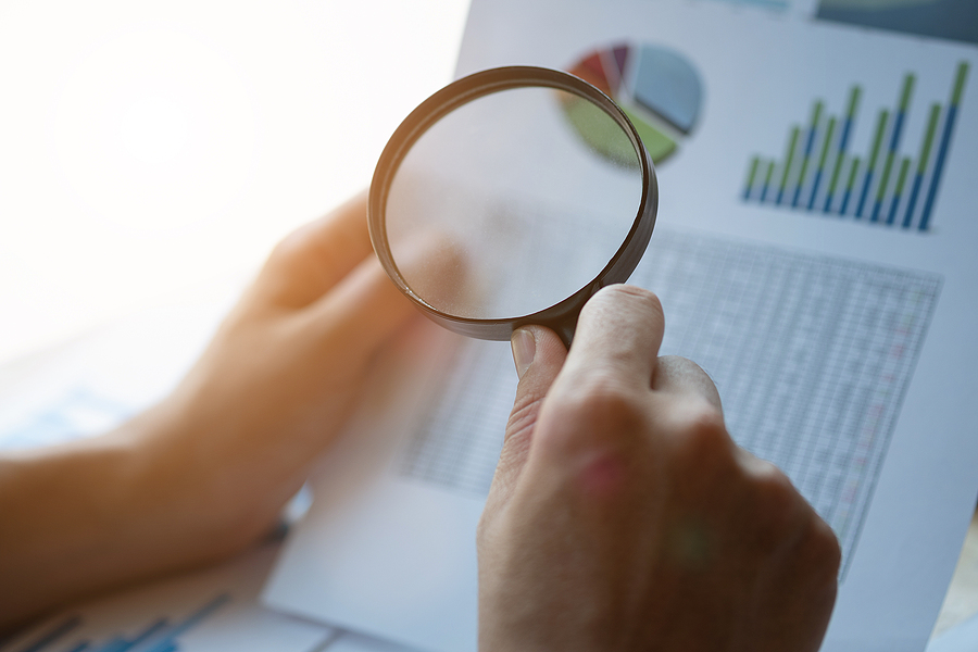 Close up of a business person examining budgets with financial documents in their left hand and a magnifying glass in their right.
