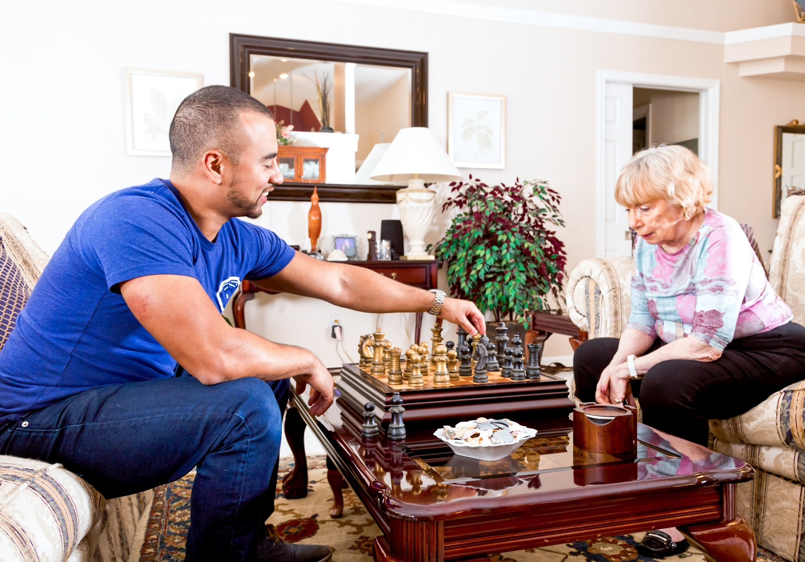 A college student playing chess with an older woman.