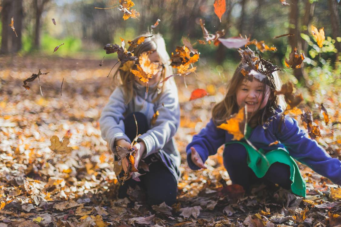 Photo of Children Playing With Dry Leaves