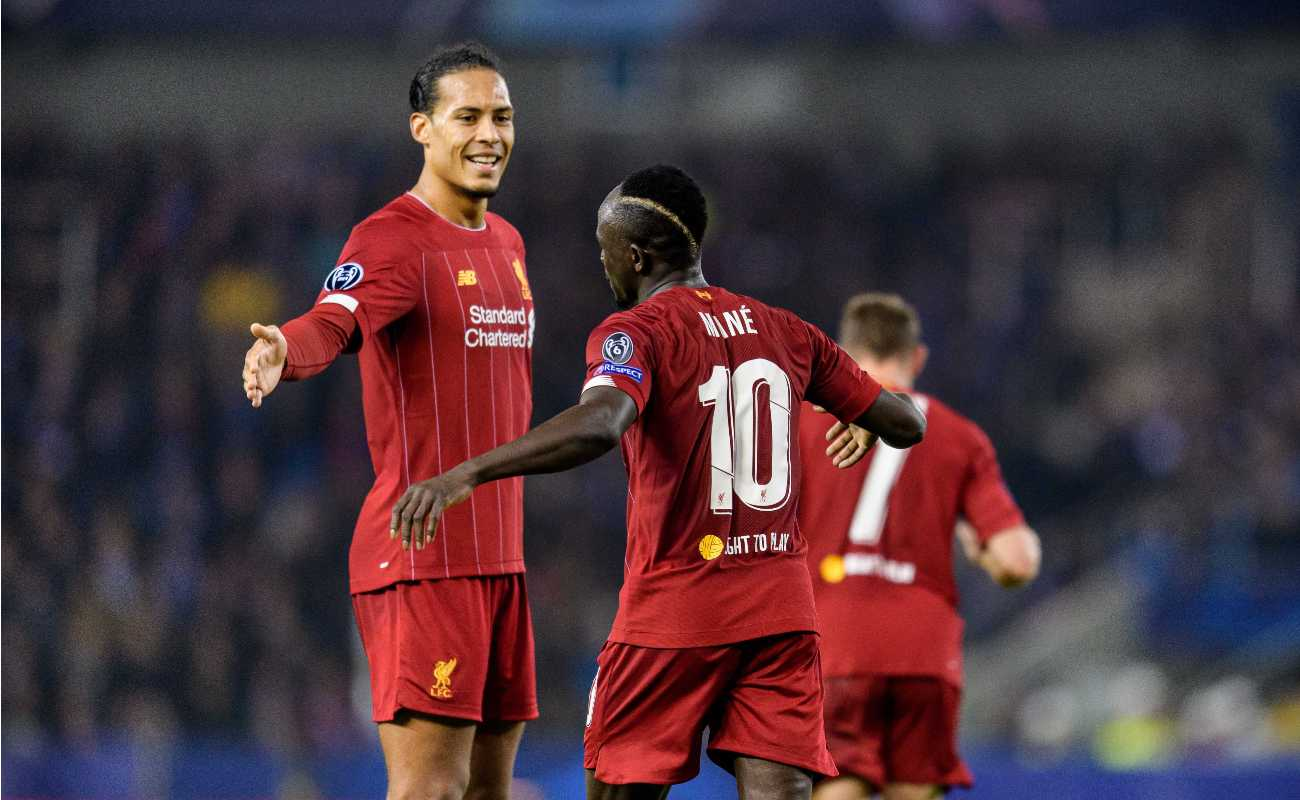 Liverpool players Virgil van Dijk and Saido Mané go in for a handshake to celebrate a goal