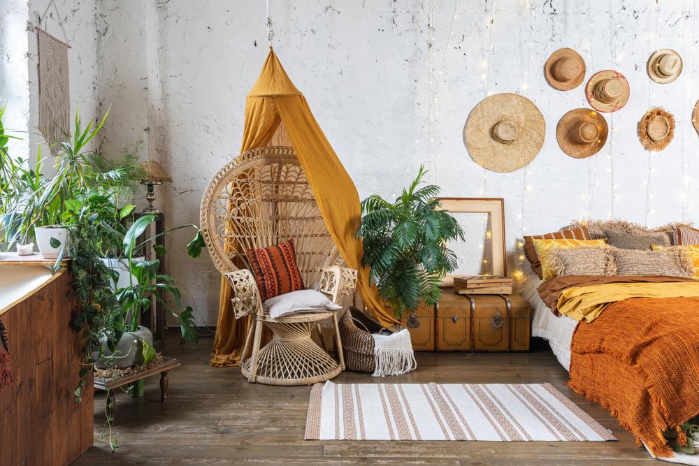 Um quarto boho com plantas, itens artesanais e vários chapeis de palha decorativos.