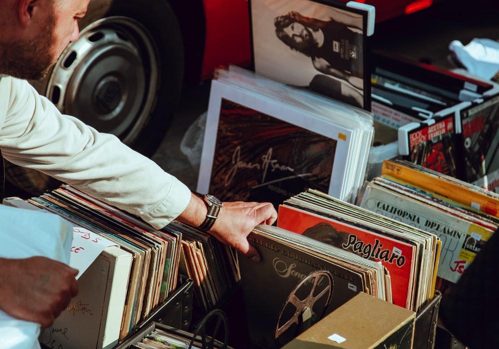 person holding vinyl records