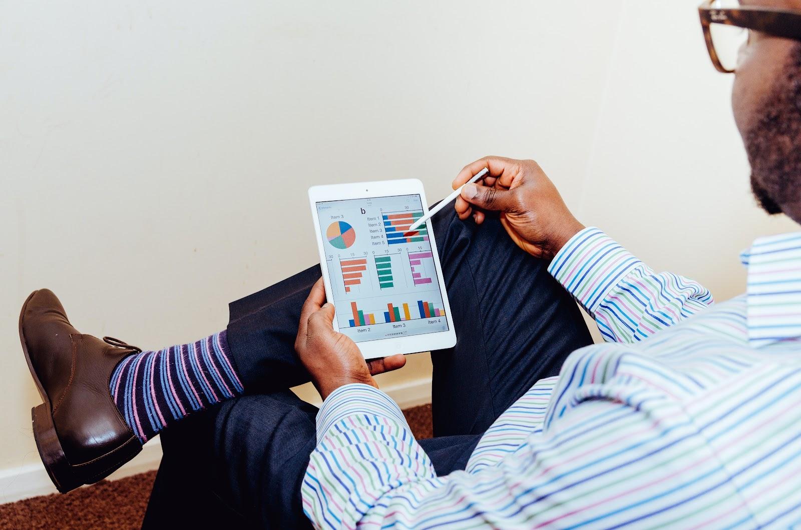 homme consultant des graphiques sur une tablettes qui représentent le taux d'engagement de son audience