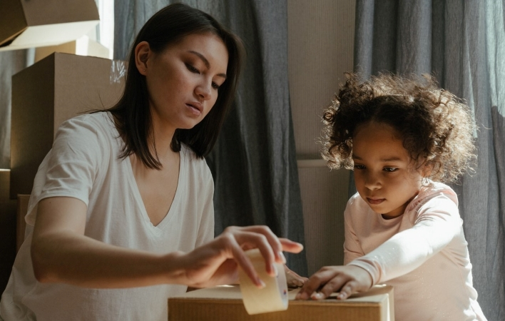 a woman and her child packing up moving boxes